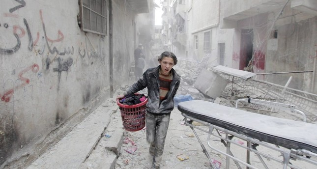 A boy carries his belongings at a site hit by a barrel bomb dropped by the Assad regime in Aleppo's al-Fardous district. (Reuters Photo)