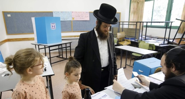 Children accompany an ultra-Orthodox Jewish man to a voting station in the city of Bnei Brak during the Israeli parliamentary election on Sept. 17, 2019 (AFP Photo)