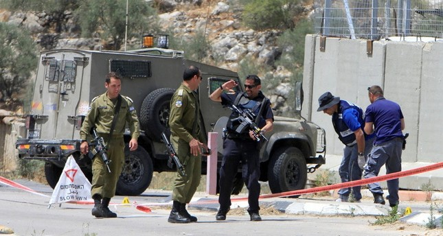 Israeli soldiers and policemen inspect the scene where a Palestinian woman was shot dead by Israeli forces at Ennab Israeli checkpoint near the West Bank city of Tulkarm June 2, 2016.emREUTERS/em