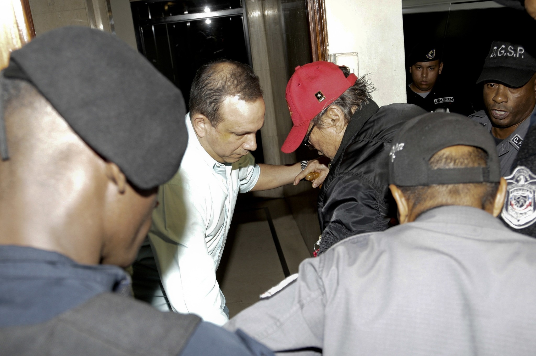 Panamanian ex-dictator Manuel Antonio Noriega, wearing a red baseball cap, arrives after being placed under house arrest for three months in Panama City. (AP Photo)