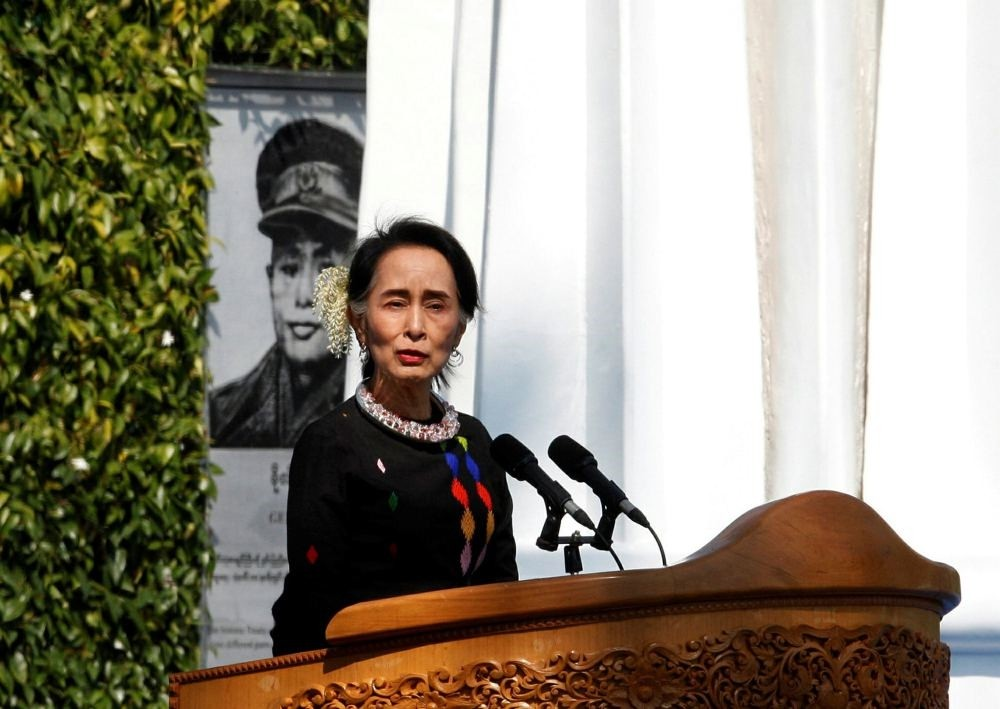 Myanmar State Counsellor Aung San Suu Kyi, standing by a portrait of her late father and national hero Gen. Aung San and the Panglong monument, delivers a speech during a ceremony to mark the 70th anniversary of Union Day in Panglong, Feb. 12.
