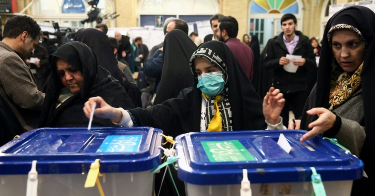 A woman wears a face mask as she casts her vote during parliamentary elections at a polling station in Tehran, Iran February 21, 2020. Nazanin Tabatabaee/WANA (West Asia News Agency) via REUTERS