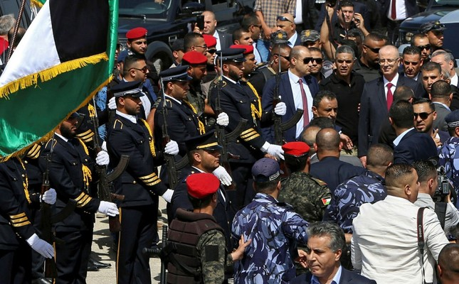 Palestinian Prime Minister Rami Hamdallah reviews an honor guard on his arrival to the Palestinian side of the Beit Hanoun border crossing in the northern Gaza Strip, Oct. 2.