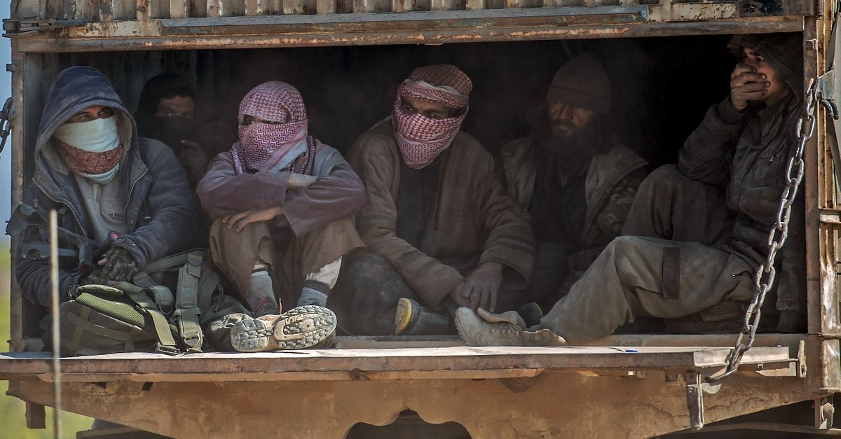 A truck carrying men, identified as Daesh members, being transported out of the terrorist organization's last holdout of Baghouz in Syria's northern Deir el-Zour province, Feb. 20, 2019.