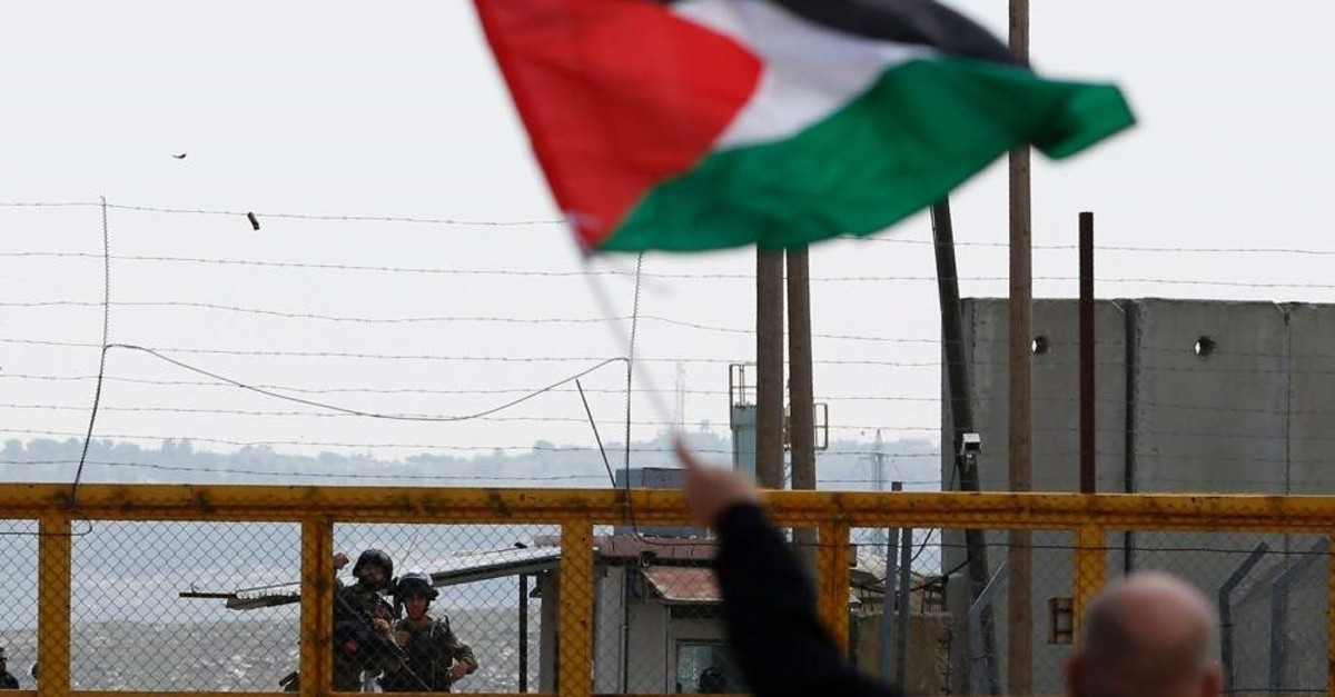 A protester waves a Palestinian flag in front of Israeli security forces outside the compound of the Israeli-run Ofer prison, the occupied West Bank, March 30, 2016. (AFP Photo)