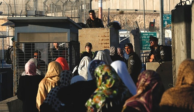 Palestinian women wait to cross through the Qalandia checkpoint near the West Bank city of Ramallah June 10, 2016, as they head to Jerusalem's Al-Aqsa mosque for the first Friday prayer of the holy Muslim fasting month of Ramadan. (AFP Photo)
