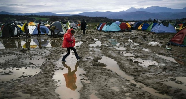 A girl walks in the mud in a makeshift camp at the Greek-Macedonian border, near the Greek village of Idomeni, March 9, 2016.