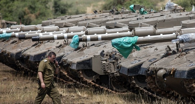 An Israeli soldier walks next to tanks deployed near the Israeli-Syrian border in the Golan Heights, May 9.