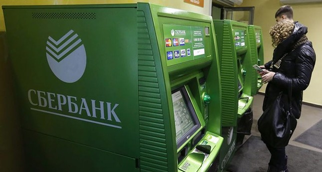 People use an automated teller machine inside a branch of Sberbank in St. Petersburg, November 5, 2014. (Reuters Photo)
