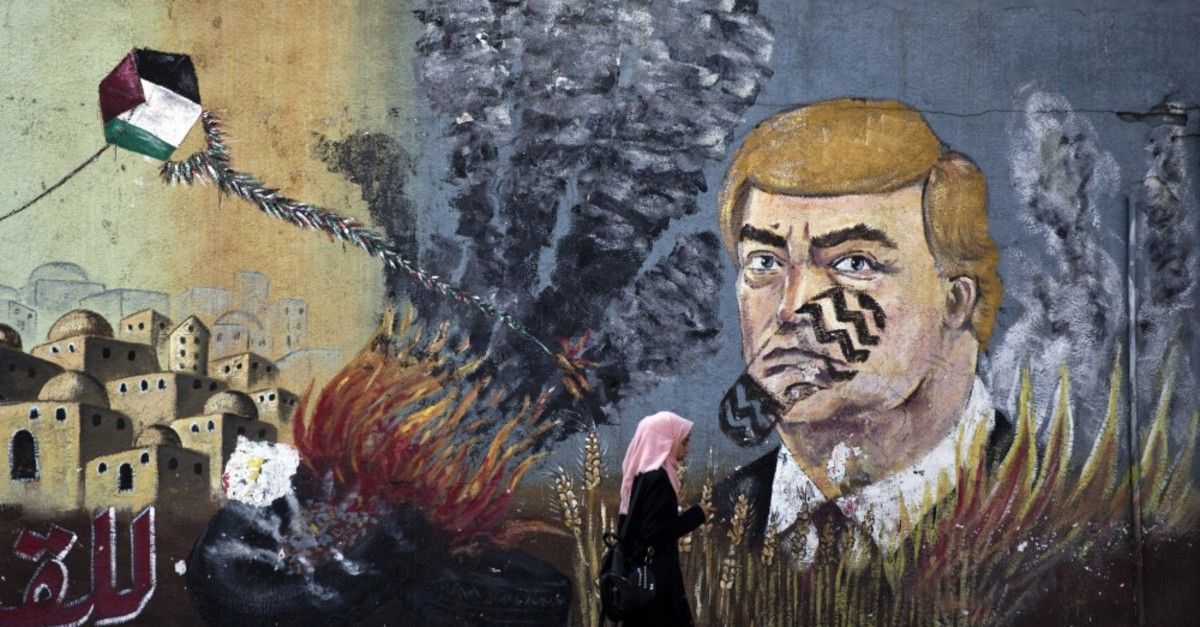 A wall with graffiti depicts U.S. President Donald Trump with a footprint on his face in Gaza City, Tuesday, June 25, 2019.