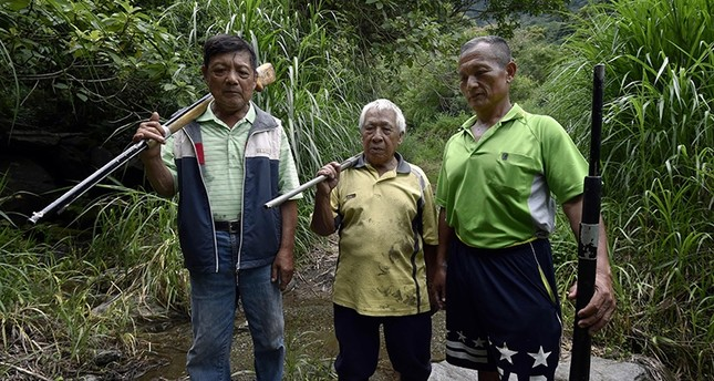 Tama Talum (R), an aboriginal hunter, poses for photos with fellow tribe hunters at a mountain in Taitung, eastern Taiwan on July 2, 2016. (AFP Photo)