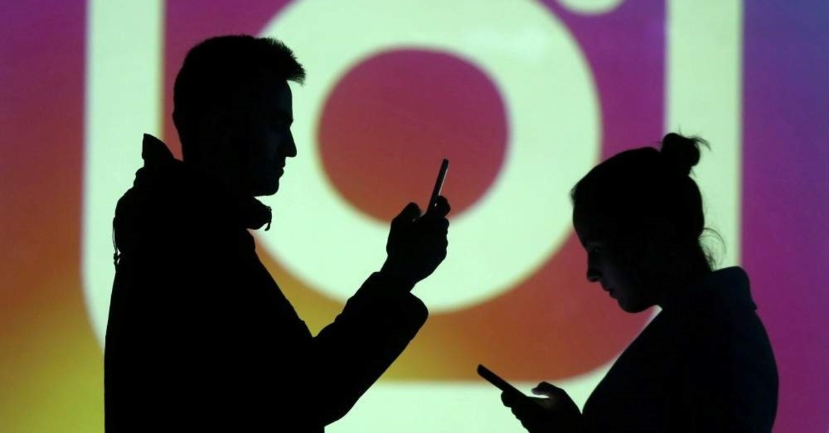 Silhouettes of mobile users are seen next to a screen projection of Instagram logo in this picture illustration taken March 28, 2018. (Reuters Photo)