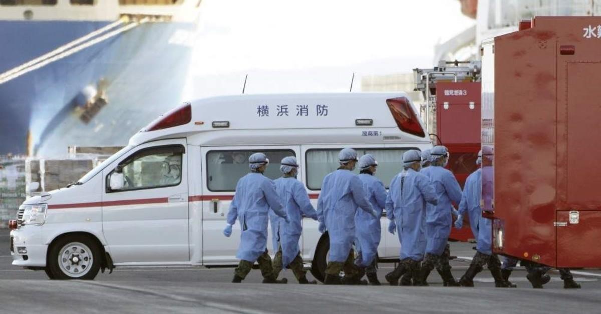 Officials walk into the cruise ship Diamond Princess anchors off the Yokohama Port Sunday, Feb. 9, 2020. (AP Photo)
