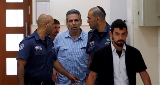 وزير الطاقة والبنى التحتية الإسرائيلي السابق غونين سيغيف (بالقميص الأزرق) في طريقه لقاعة المحكمة (AP)
