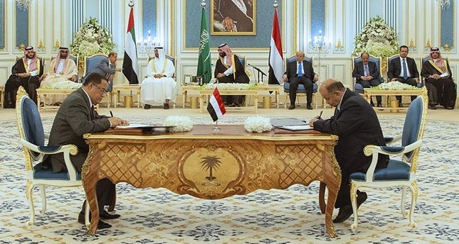 A handout picture provided by the Saudi Royal Palace on November 5, 2019, shows Yemeni Southern Transitional Council (STC) member and former Aden governor Nasser al-Khabji, and Yemen's deputy prime minister Salem al-Khanbashi, sign documents during a peace-signing ceremony