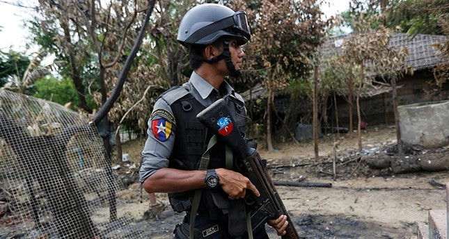 A police officer guards near a house which was burnt down during the last days of violence in Maungdaw, northern Rakhine State, Myanmar Aug. 30, 2017. (Reuters Photo)