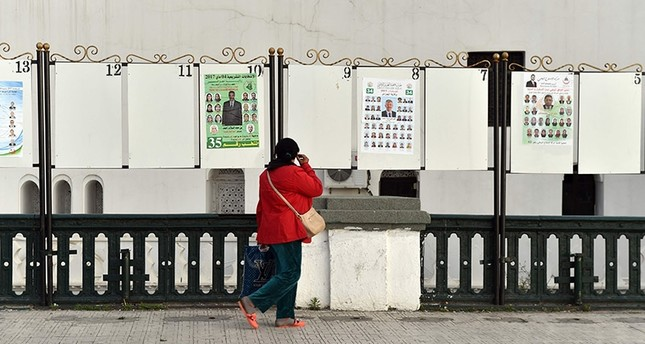 An Algerian woman looks at electorial campaign posters for the upcoming legislative elections in Algiers' Martyrs Square as the official start of campaigning got underway on April 9, 2017. (AFP Photo)