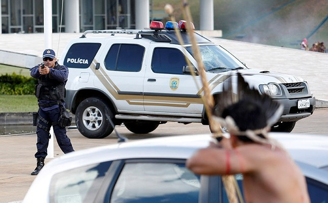 Riot police points his gun at Brazilian Indians during a demonstration against the violation of indigenous people's rights, in Brasilia, Brazil, April 25, 2017. (Reuters Photo)