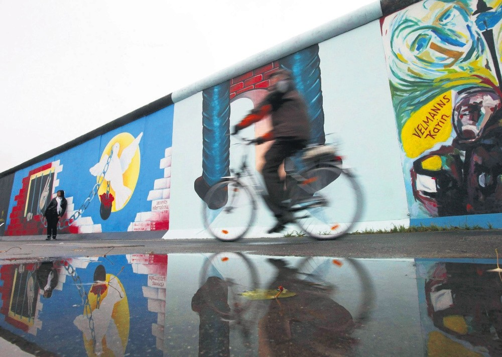 A cyclist passes a segment of the East Side Gallery in Berlin.