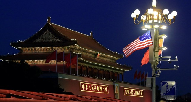 People walk under U.S. and Chinese flags at the Forbidden City during the visit by U.S. President Donald Trump in Beijing, China, November 8, 2017.