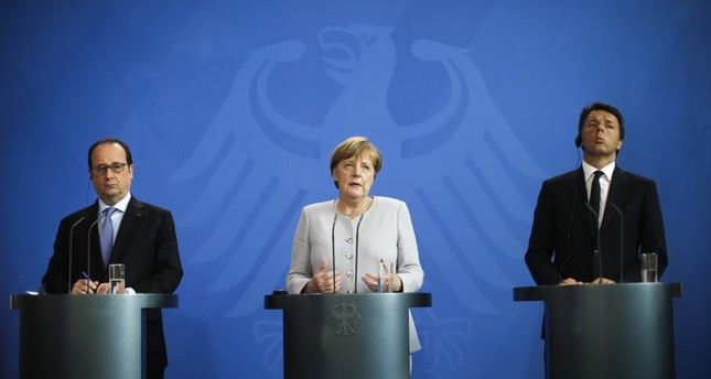 France's President François Hollande, (L), German Chancellor Angela Merkel, (C) and the Prime Minister of Italy Matteo Renzi, (R), brief the media during a meeting at the chancellery in Berlin on June 27.