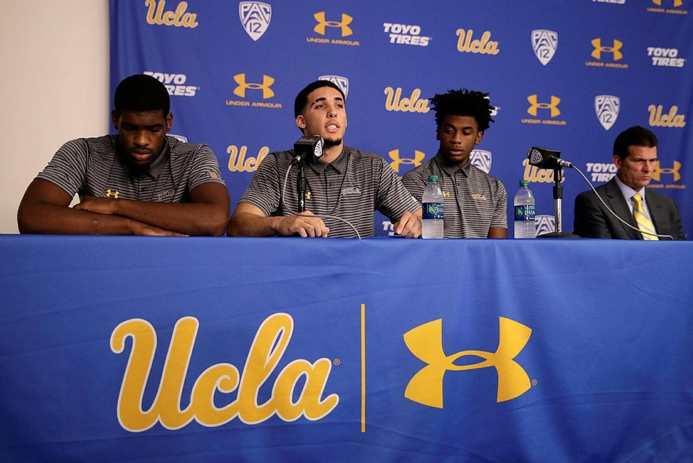 Flanked by Cody Riley, left, and Jalen Hill, third from left, UCLA basketball player LiAngelo Ball reads his statement as head coach Steve Alford listens during a news conference at UCLA, Nov. 15, 2017, Los Angeles, Calif., U.S. (AP Photo)