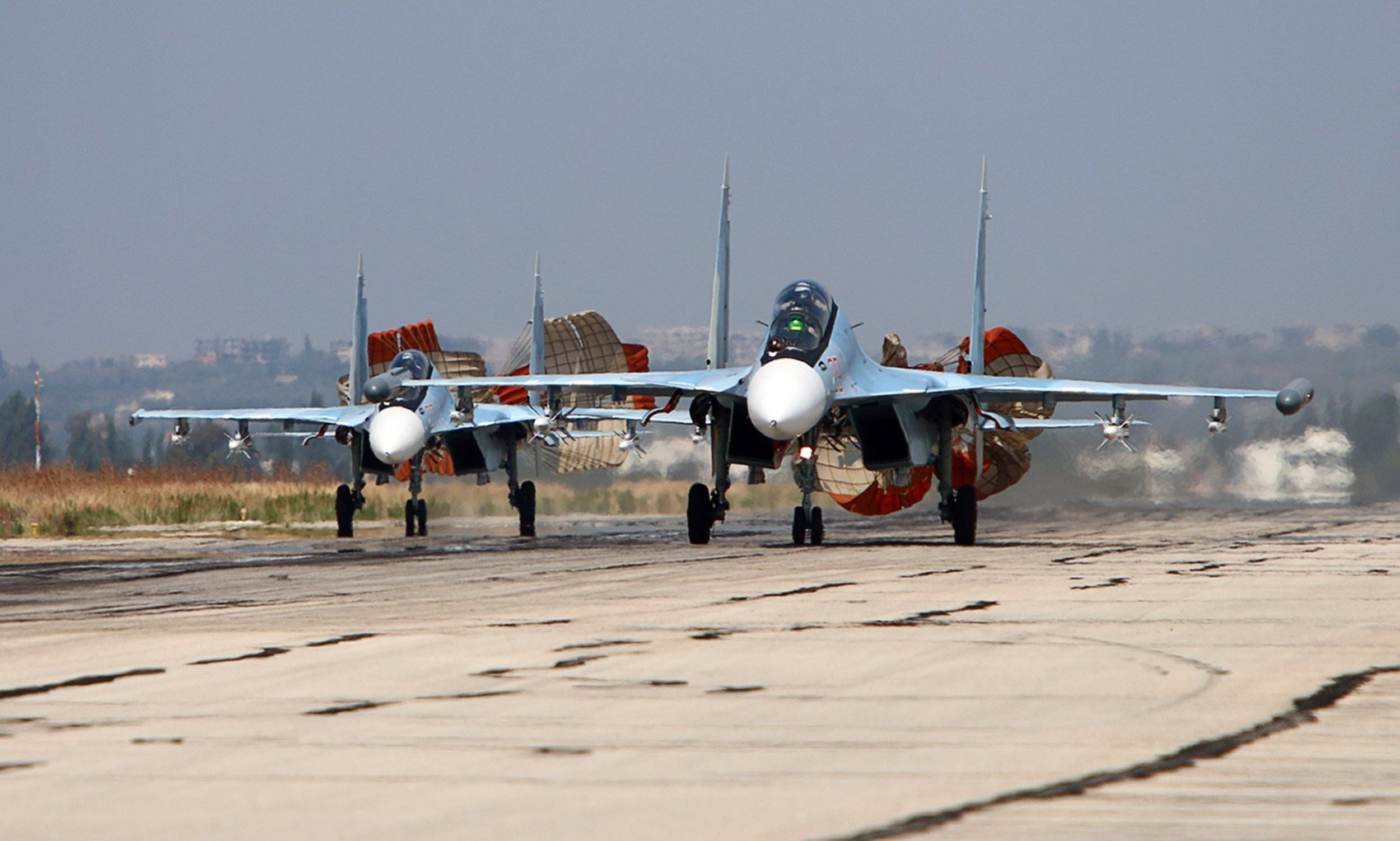Russian Sukhoi SU-30 SM jet fighters landing on a runway at the Hmeimim airbase in the Syrian province of Latakia. (AFP PHOTO)