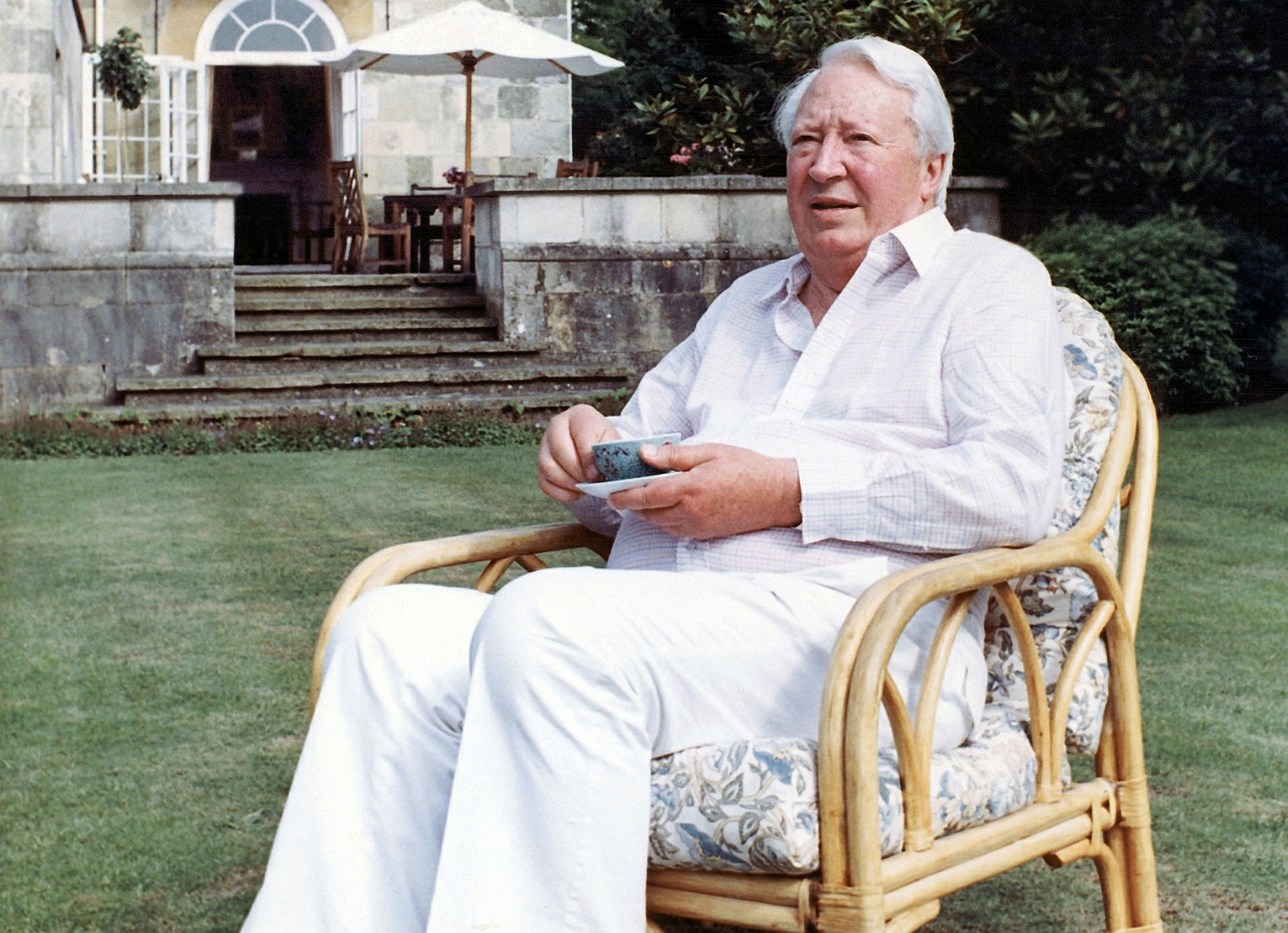 This is a July 19, 1989 file photo of former British Prime Minister Edward Heath as he takes tea in the garden of his home in Salisbury, England. (AP Photo)