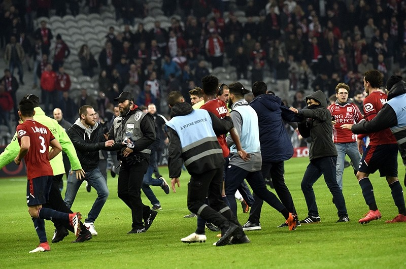 Lille' supporters invade the pitch at the end of  the French L1 football match between Lille and Montpellier (AFP Photo)