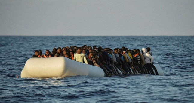 Migrants and refugees on a rubber boat off the Libyan coast in the Mediterranean Sea.