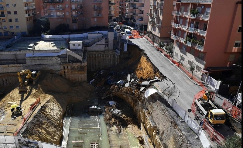 The picture taken on February 15, 2018 in the street of Balduina's district in Rome shows a huge sinkhole that opened up the day before in Rome, swallowing six cars. (AFP Photo)