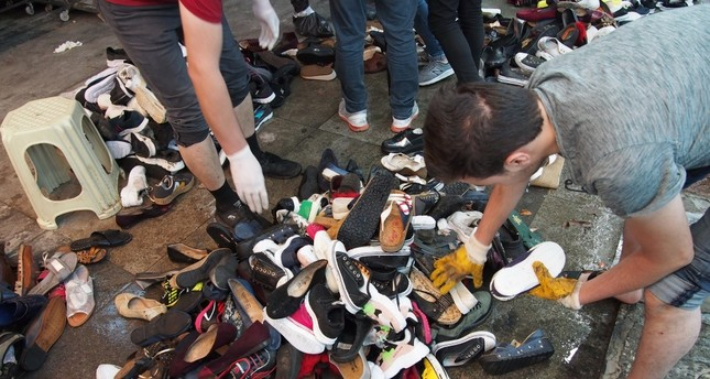 Shopkeepers sort out shoes salvaged from the floods at an underpass lined with shops in Eminönü, Aug. 21, 2019.