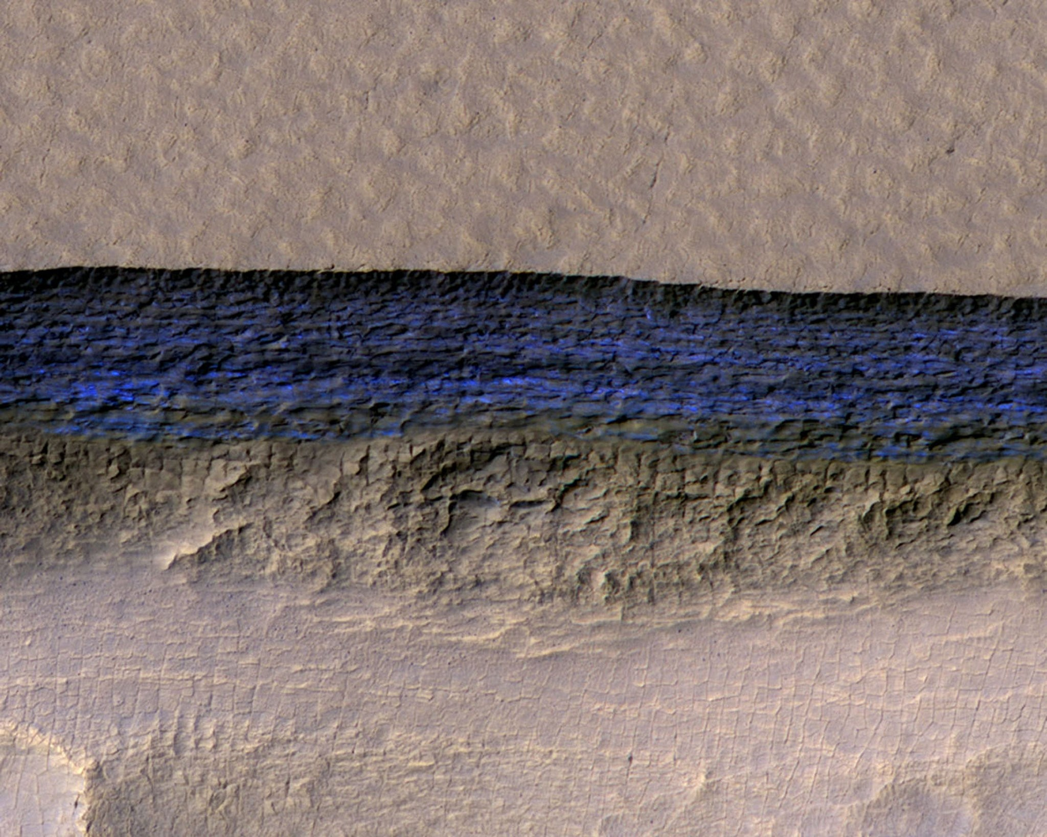 A cross-section of a thick sheet of underground ice is exposed at the steep slope that appears bright blue in this enhanced-color view of Mars from the HiRISE camera on NASA's Mars Reconnaissance Orbiter on January 11, 2018. (REUTERS Photo)