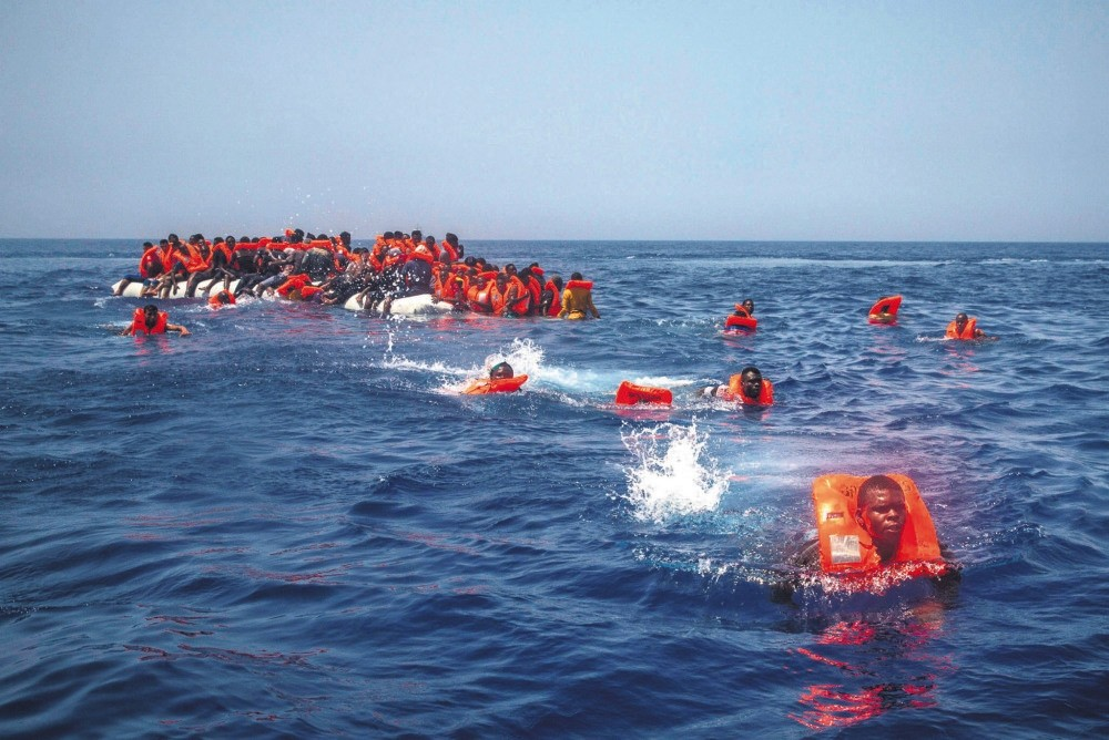 African migrants try to reach a Spanish NGO Proactiva Open Arms rescue ship after falling from a punctured rubber boat in the Mediterranean Sea, about 12 miles north of Sabratha, Libya, July 23.