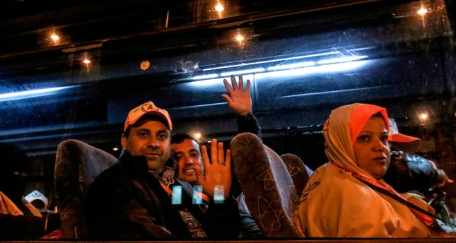 Palestinians Muslim pilgrims wave to their relatives as they sit in a bus at the Rafah border crossing between the Gaza Strip and Egypt before crossing to depart for umrah pilgrimage for the first time since 2014, Sunday, March 3, 2019. AFP Photo