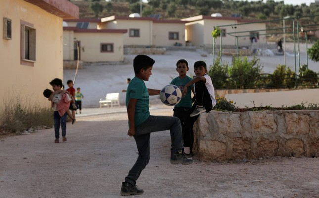Children play near apartments built for people who lost family members during the war, in the Idlib countryside, June 10, 2019.
