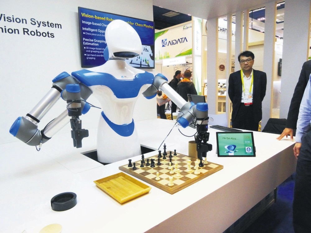 A robot developed by Taiwan engineers moves chess pieces on a board against an opponent at the 2017 Consumer Electronic Show in Las Vegas, Nevada.