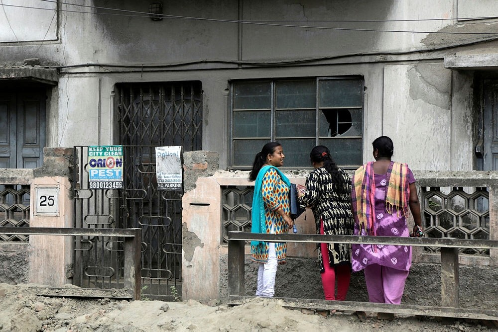 Indian women stand outside the house where a 46-year-old Subhabrata Majumdar had allegedly kept his mother's body in a freezer for almost three years while collecting her monthly pension payments in Kolkata, India, Friday, April 6, 2018. (AP Photo)