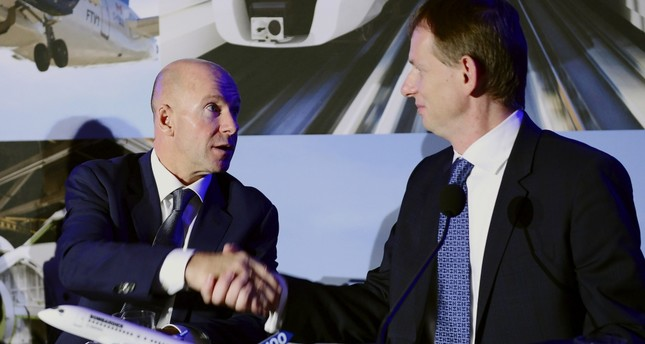 Bombardier CEO Alain Bellemare (L), and president Canada and COO of North America for Airbus Helicopters Romain Trapp shake hands during a press conference in Montreal on Monday.