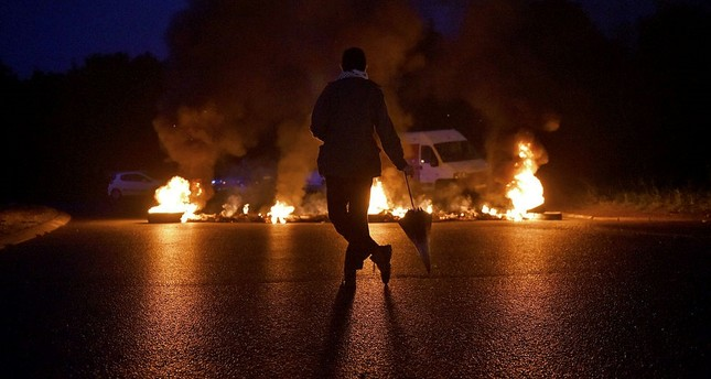 A protestor looks at a fire displayed on a traffic circle as union trade members block trucks on September 25, 2017 in Donges, western France. AFP Photo