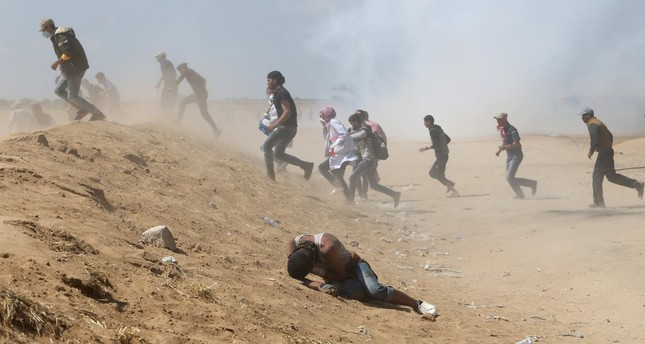 A Palestinian demonstrator reacts as others run from tear gas fired by Israeli forces during a protest marking the 70th anniversary of Nakba, at the Israel-Gaza border in the southern Gaza Strip yesterday.