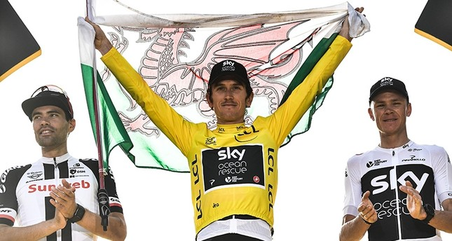 Tour de France 2018 winner Great Britain's Geraint Thomas (C), holds a Welsh flag and the overall leader's yellow jersey, next to second-placed Netherlands' Tom Dumoulin (L) and third-placed Great Britain's Christopher Froome (R). (AFP Photo)