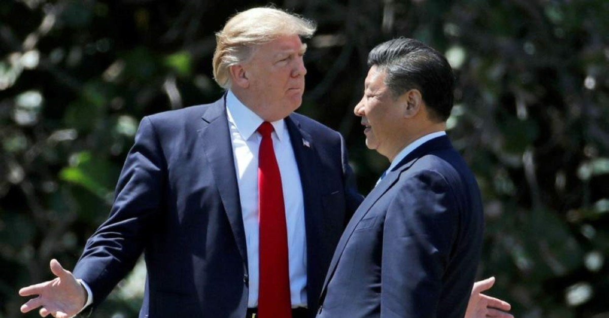 U.S. President Donald Trump, (L) gestures as he and Chinese President Xi Jinping walk together at Mar-a-Lago in Palm Beach on April 7, 2017. (AP Photo)
