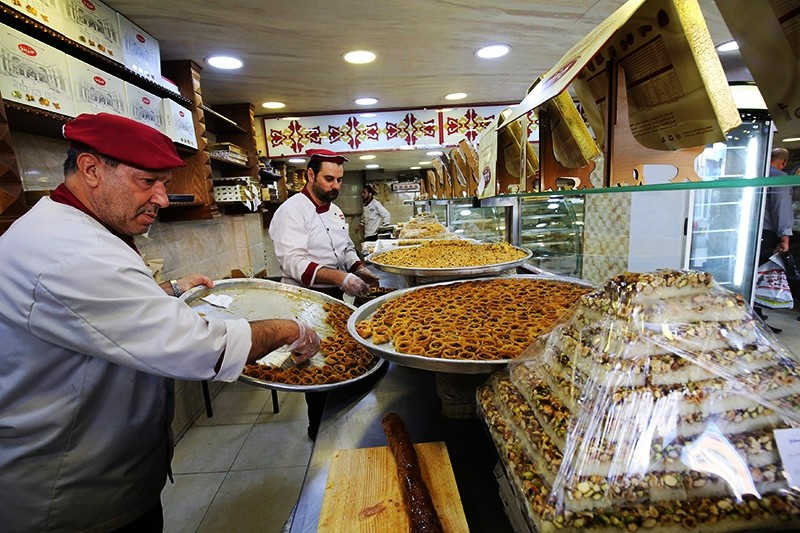 Men work at a shop selling traditional Syrian sweets, that is owned by Syrian refugee Mazen Obeido who fled the conflict in his homeland, in the northern Jordanian town of Irbid. ( AFP Photo)