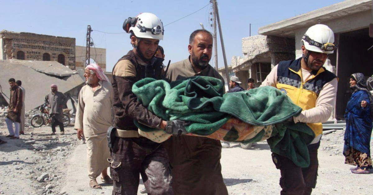 This photo provided by the Syrian Civil Defense group, shows workers carrying a victim after a deadly airstrike hit a market killing several people in the village of Ras el-Ain, in the northwestern province of Idlib, Syria, May 7, 2019. (AP Photo)