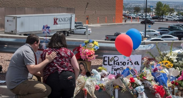 People pray beside a makeshift memorial outside the Cielo Vista Mall Wal-Mart (background) where a shooting left 20 people dead in El Paso, Texas, on August 4, 2019. (AP Photo)