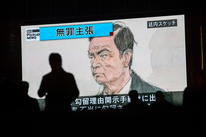 In this photo taken on Jan. 8, 2019, pedestrians pass by a television screen showing a news program displaying a sketch of former Nissan chief Carlos Ghosn in the courtroom, in Tokyo, as the headline reads in Japanese ,Innocence claim.,  (AFP Photo)