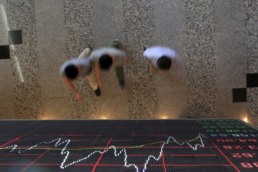 People walk under an electronic board showing stock information at the Shanghai Stock Exchange in Lujiazui Financial Area.