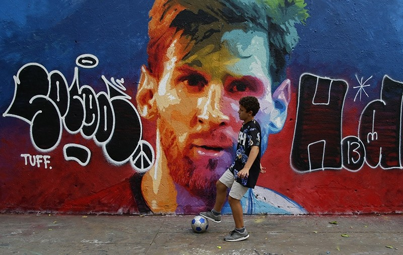 A boy plays football in front of a graffiti image of FC Barcelona player Lionel Messi in Barcelona, Spain, Thursday, June 15, 2017. (AP Photo)
