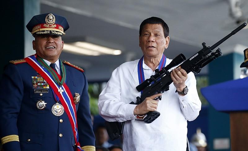 In this April 19, 2018 file photo, Philippine President Rodrigo Duterte jokes to photographers as he holds an Israeli-made Galil rifle. (AP Photo)